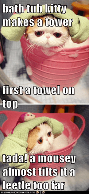 bath tub kitty makes a tower first a towel on top tada! a mousey almost tilts it a leetle too far