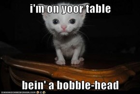 i'm on yoor table  bein' a bobble-head